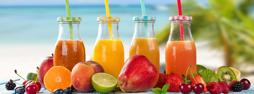 fruit smoothies in class bottles with fruit in front of them by the beach